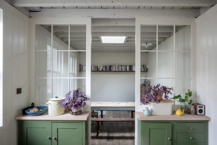 Muebles de cocina pintados de verde con mesada de madera