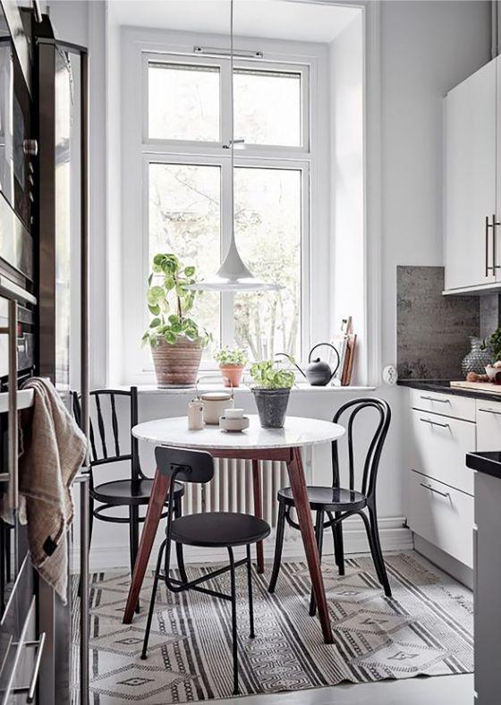Comedor integrado en la cocina con mesa pequeña redonda y sillas en diferentes estilos