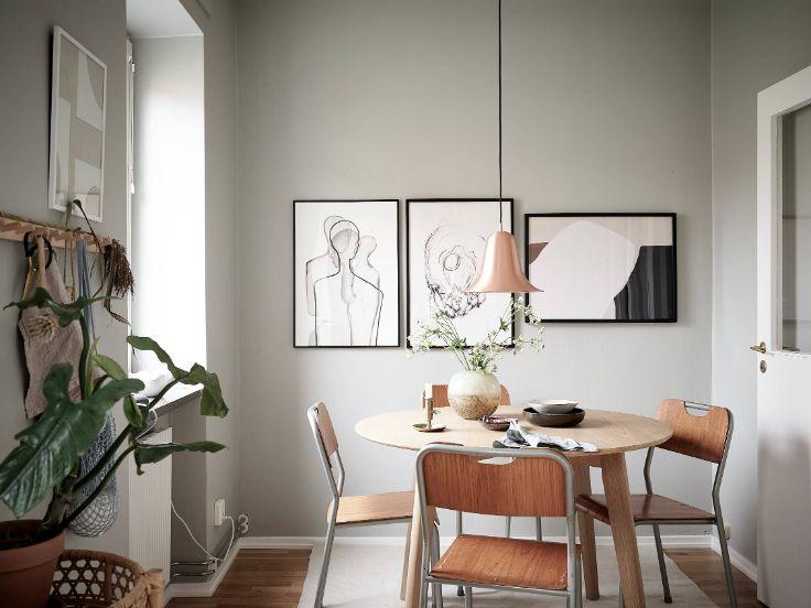 Cuadros, alfombras y una lámpara de cobre delimitan visualmente el espacio del comedor
