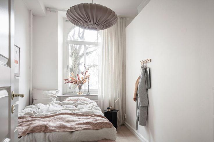 Dormitorio con espacio para una cama doble nada más, con ventana haciendo de cabecera