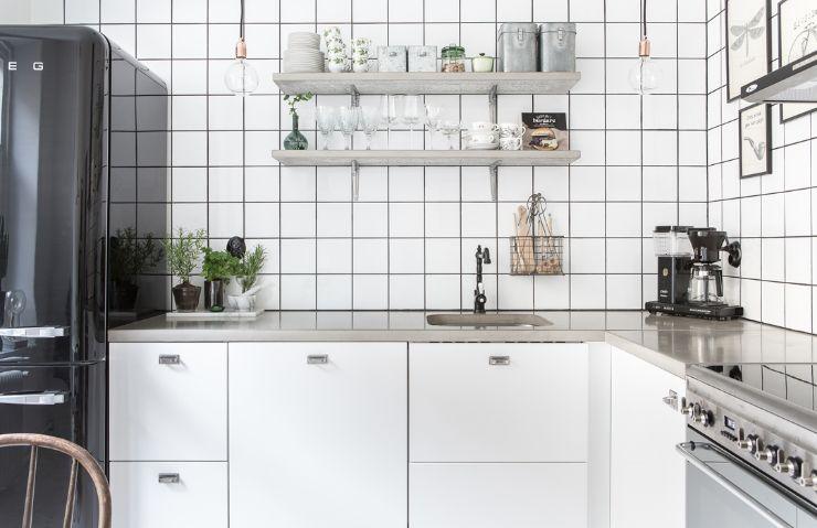 Cocina con mesada de cemento alisado y muebles blancos