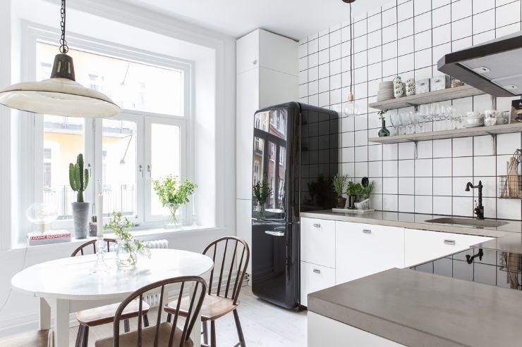 La mesada de cemento, los azulejos con juntas color negro y la refrigeradora Smeg negra dan a la cocina un aire moderno e industrial