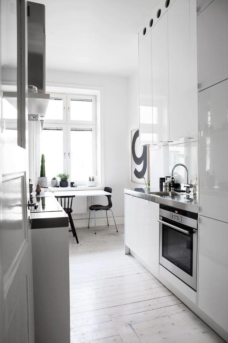Cocina con mesadas de acero inoxidable y muebles blancos brillante aportan estilo moderno al diseño