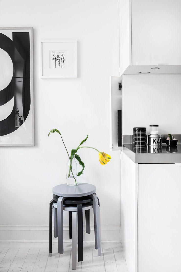 Paleta de color basada en el blanco, negro y gris está presente en la decoración de la cocina y todo el departamento