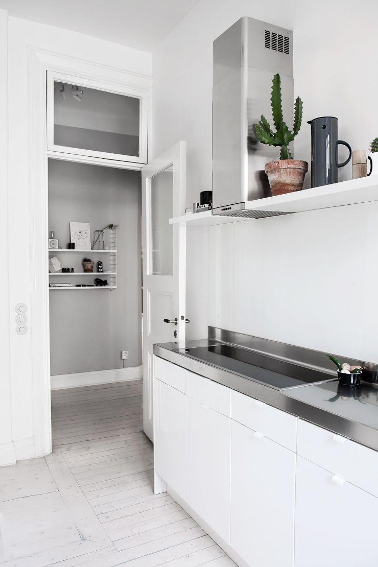 Cocina con mesadas de acero inoxidable y muebles blancos modernos