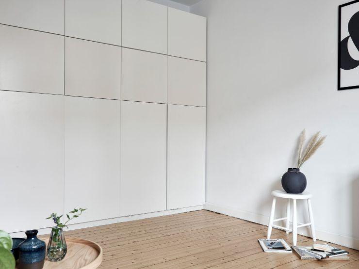 Sector del dormitorio con la cama sin desplegar. El diseño del mueble y el color blanco ayudan a que se integre a la decoración del resto del ambiente