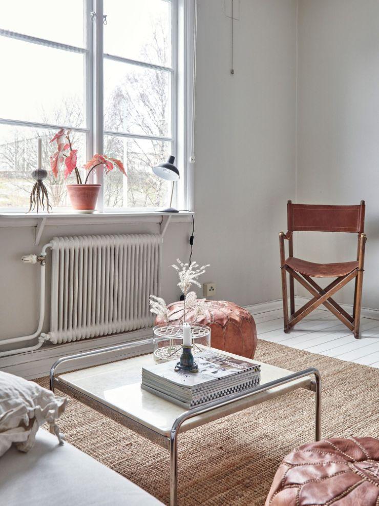 Para que la decoración minimalista no sea tan fría se incorporan muebles y accesorios en tonalidades cálidas como la alfombra, los puffs, el sillón plegable de madera, etc.