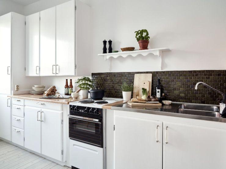 Muebles de cocina blancos y alacenas. Al dejar una parte de la pared libre de alacenas se logra una decoración más relajada y liviana visualmente