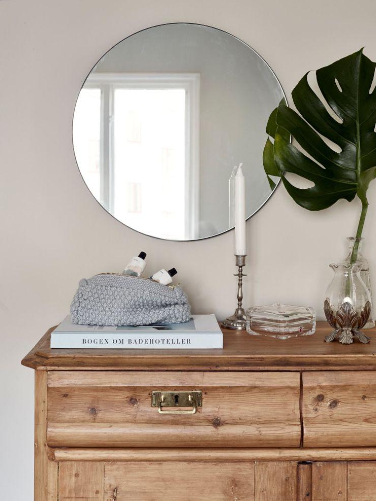 Accesorios decorativos como espejos, candelabros y floreros complementan la decoración de la sala