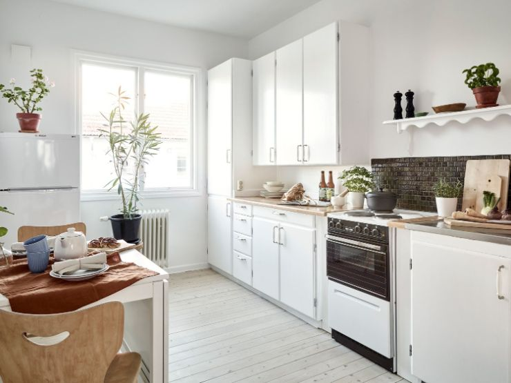 Cocina pequeña y luminosa gracias a los tonos claros utilizados en paredes, muebles, alacenas y pisos de pino blanqueado